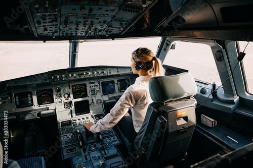 Slika na platnu Woman pilot sitting in aircraft cockpit, flying the plane.