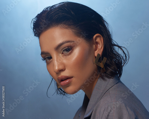 Closeup fashion face studio portrait. Tanned caucasian brunette woman. Fashionable stylish female model with makeup and wet hair against smoke at background