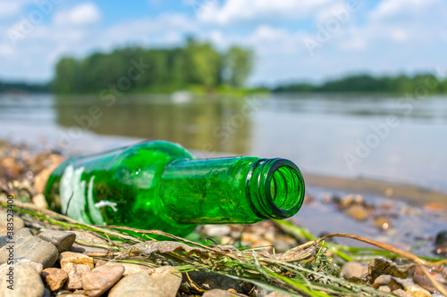 Valokuvatapetti Glass bottle thrown ashore pollutes and harms nature