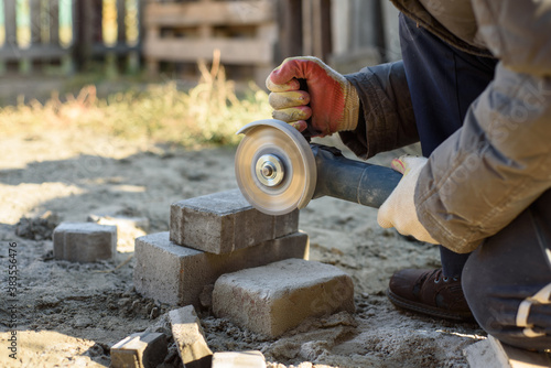 Fotografie, Tablou A man saws off paving stones with an angle grinder. Street work
