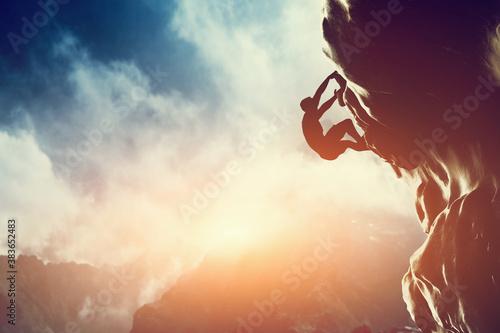 A silhouette of man climbing on rock, mountain at sunset. Fototapet