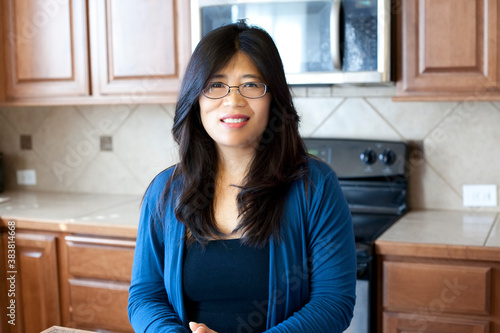 Beautiful Asian woman in early forties standing in kitchen