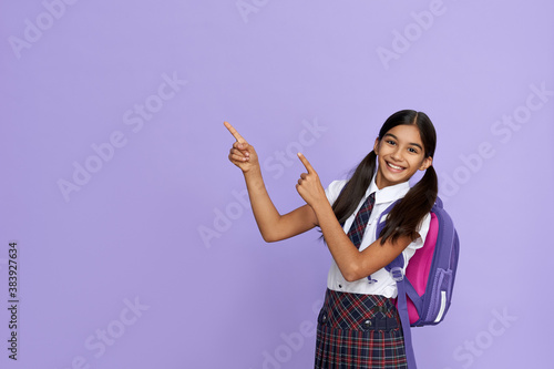 Canvas Print Happy indian kid primary elementary school girl with backpack wearing school uniform pointing fingers aside at copy space advertising products or services for pupils isolated on violet background