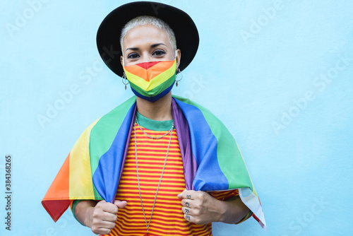 Canvas Print Portrait of gay young woman with mask wearing a rainbow flag - Lgbt concept - Fo
