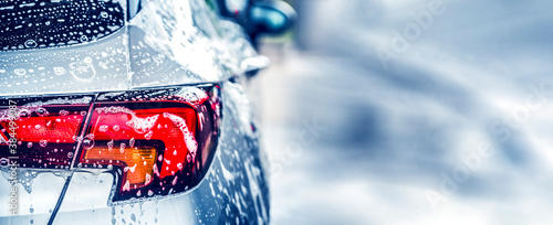 Manual car wash with white soap, foam on the body. Washing Car Using High Pressure Water.