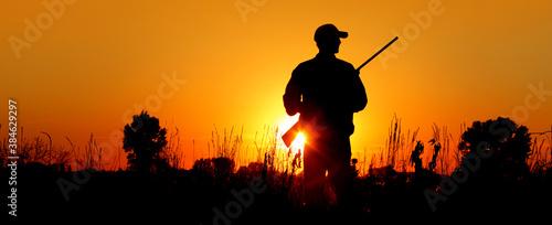 Tablou Canvas A silhouette of a male hunter carrying a shotgun