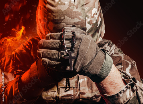 Fotografie, Tablou Photo of a military soldier in uniform and armor helmet sitting and holding cross religious necklace on back background with red fire burning glow
