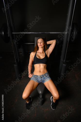 Foto Beautiful sportive brunette woman having rest ath the bench by smith machine in