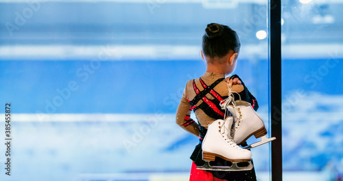 Fototapeta premium Back view portrait of little girl holding figure skates standing by ice rink and watching training, copy space