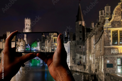 Photographie Tourist taking photo of Bruges old town with it's historic buildings and canals