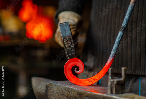 The blacksmith twists the spiral with a sledgehammer, placing a red-hot iron blank on the anvil Fototapeta
