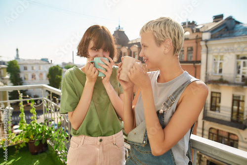 Canvas Print Two cheerful women drinking coffee or tea while standing on the balcony