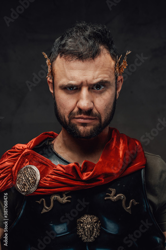 Fotografia Serious and bearded roman emperor dressed in dark armour and red cloak
