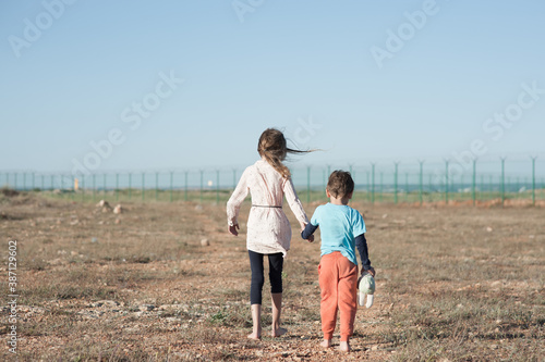 Canvas-taulu two poor kids family brother with toy and thin sister refugee illegal migrant wa