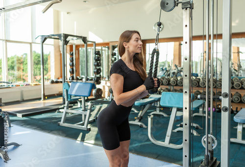 Young sexy fit woman with perfect body in sportswear trains triceps in crossover cable exercise machine at modern gym