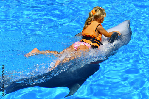 A little girl rides a dolphin in the pool of the oceanarium with blue water. Joy. Pleasure. Plays with a cute sea whale.