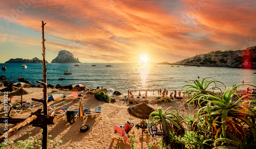 Picturesque view of Cala d'Hort tropical Beach, people hangout in beautiful beach with Es Vedra rock view during magnificent vibrant sunset glowing sun. Balearic Islands, Spain, Espana. Ibiza