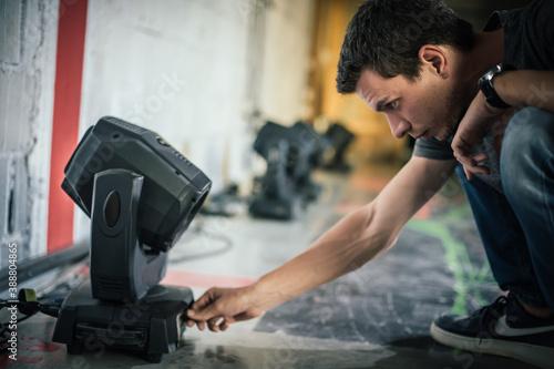 Fotografering Theater lighting technician electric engineer adjusting focus of lighting elements backstage