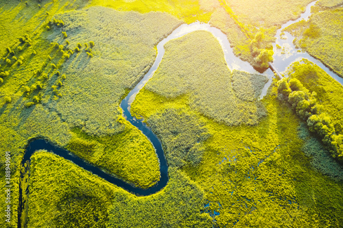 Canvas Print Aerial drone view of winding river in green field