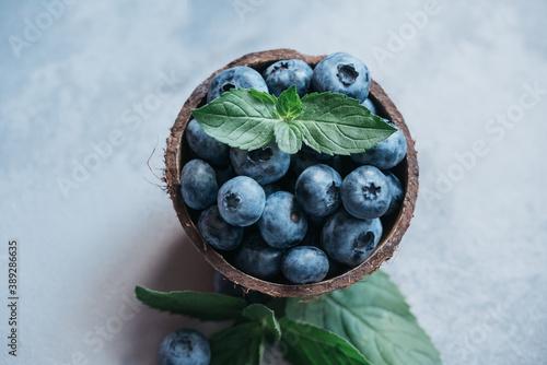 Obraz na plátně Freshly picked blueberries in coconut bowl on dark background