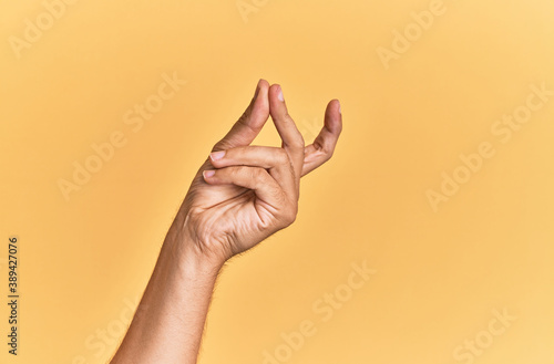 Obraz na płótnie Arm and hand of caucasian man over yellow isolated background snapping fingers f