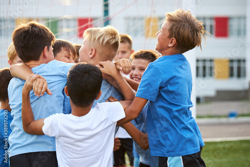 Fototapeta cheerful boys have fun after winning in football game, young kids hug each other