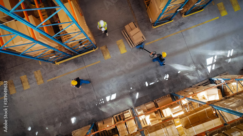 Fotografía Top-Down View: In Warehouse People Working, Forklift Truck Operator Lifts Pallet with Cardboard Box