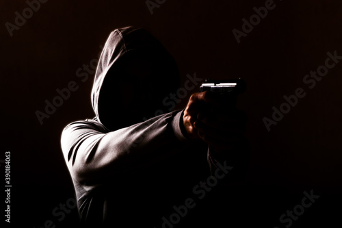 Canvas Print dangerous hooded man threatens with a pistol shot in his hands