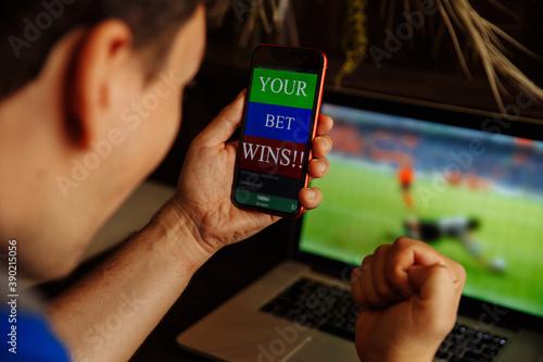 Man being happy winning a bet in online sport gambling application on his mobile phone Fototapeta