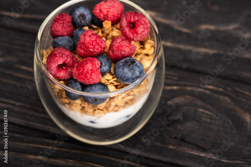 Fototapeta delicious granola with berries and yogurt in glass cup on wooden surface