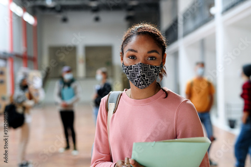 Foto African-american student with face mask back at college or university, coronavirus concept