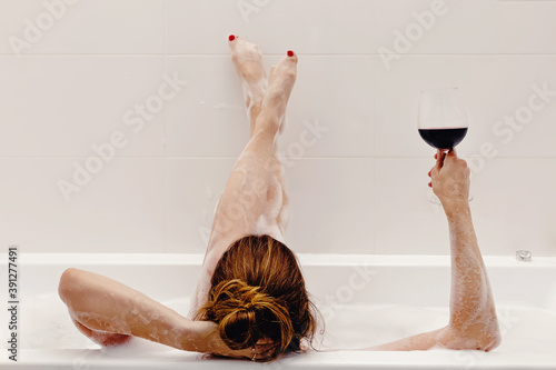 Foto Woman drinking red wine while taking bath with foam