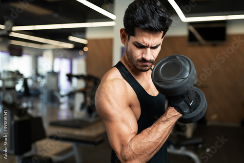Foto Strong young man flexing his biceps in the gym