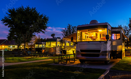 Fotografija Rving at a resort in the evening lighted sky with class A rigs interior lights o