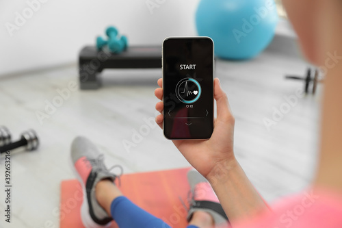 Fotografia Young woman using fitness app on smartphone indoors, closeup