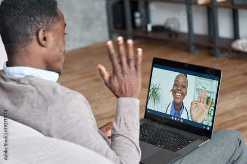Fotografija Male black patient talking on conference video call to female african doctor