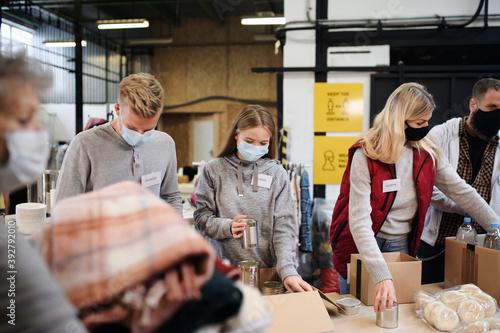Billede på lærred Group of volunteers in community charity donation center, food bank and coronavirus concept