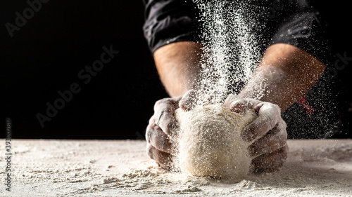Photographie Hands of baker kneading dough isolated on black background