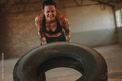Fotografia, Obraz Tough woman doing tire flip workout