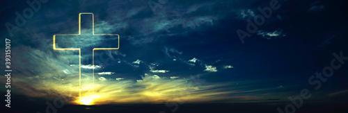 Fotografia Silhouette of shining cross on sunset, sunrise background