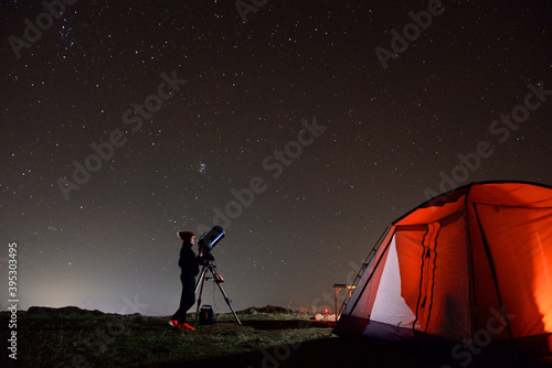 Photo Young woman fond of astronomy observing through her telescope