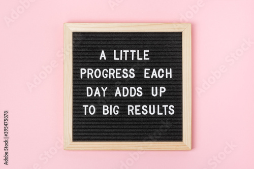 A little progress each day adds up to big results. Motivational quote on black letter board on pink background. Concept inspirational quote of the day. Greeting card, postcard.
