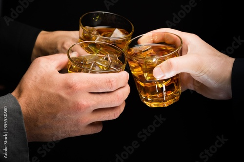 Obraz na plátne Closeup of Hands Toasting with Whiskey Glasses