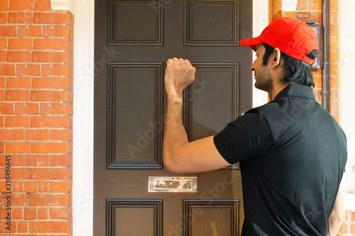 Delivery person knocking the door to deliver the order Fototapete