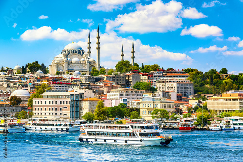 Canvas Print Touristic sightseeing ships in Golden Horn bay of Istanbul and view on Suleymaniye mosque with Sultanahmet district against blue sky and clouds