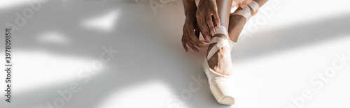 Photo cropped view of graceful african american ballerina in pointe shoes sitting on f