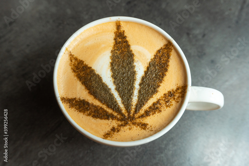 Photo of coffee in a mug with cannabis leaf on the top of it on a gray table Fototapet