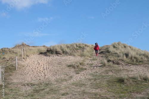 Canvas Beautiful coast landscape of sandy grass dunes with female lone figure in red co