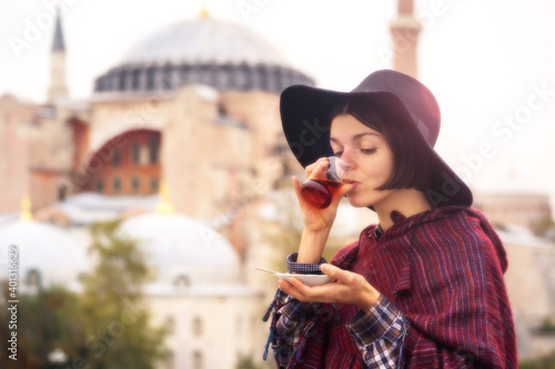 Fotografie, Obraz A young girl in a hat and poncho holds traditional Turkish tea in her hands