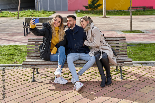 Fotografie, Obraz Three young smiling friends sitting on a park bench